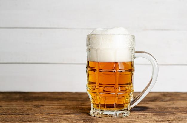 Plein verre de bière blonde sur fond de bois blanc