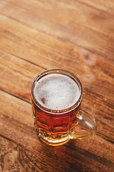 Plein verre de bière blonde sur fond rustique en bois