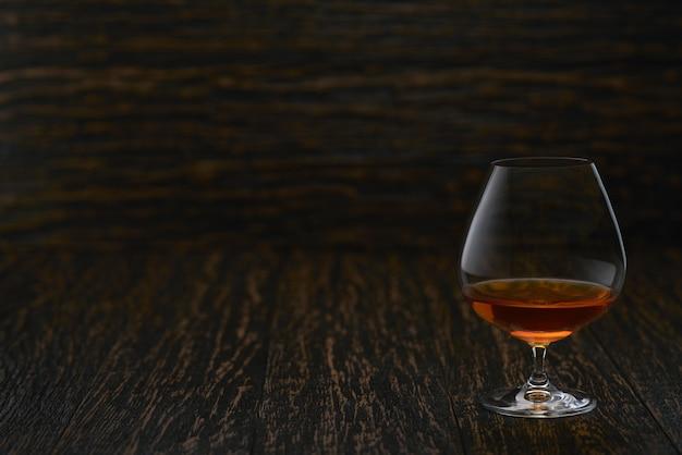 Plein verre de cognac sur une table en bois avec fond