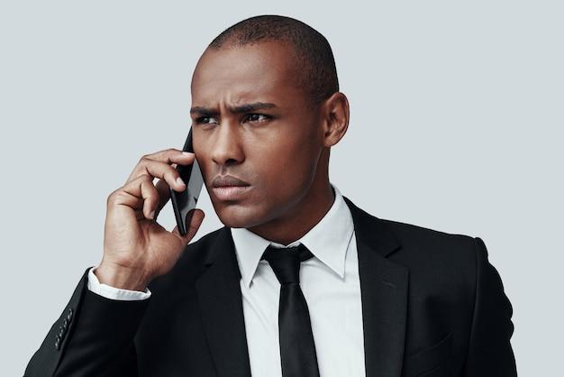 Pleine concentration. gentil jeune homme africain en tenue de soirée parlant au téléphone intelligent et fronçant les sourcils en se tenant debout sur fond gris