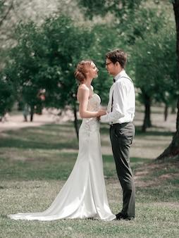 En pleine croissance. heureux jeunes mariés se tiennent ensemble dans un sunny park.