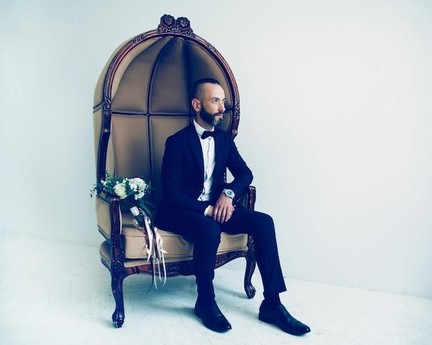 En pleine croissance. homme élégant assis sur une chaise à côté d'un bouquet de fleurs. personnes et événements