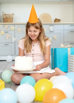 Pleine fille souriante tenant un gâteau