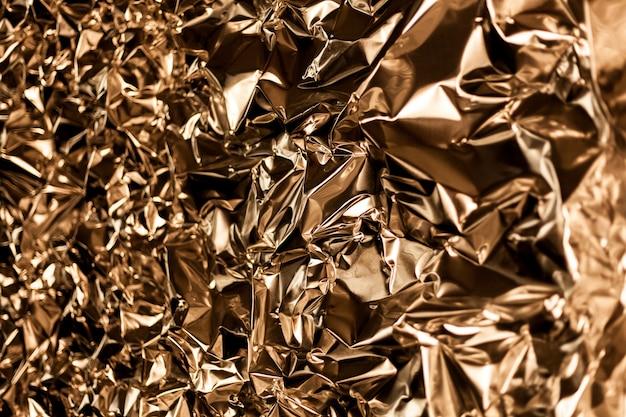 Pleine image prend une feuille de papier d'aluminium or froissé