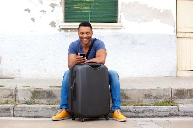 Pleine longueur beau jeune homme africain assis avec valise et téléphone intelligent