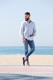 Pleine longueur bel homme tenant des lunettes de soleil et debout sur la plage