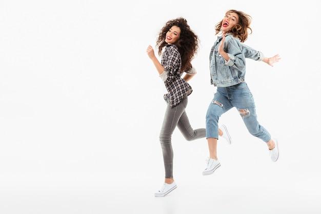 Pleine longueur deux filles espiègles courir ensemble sur un mur blanc