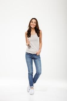 Pleine longueur femme brune heureuse avec bras dans la poche montrant le pouce vers le haut et regardant la caméra sur gris
