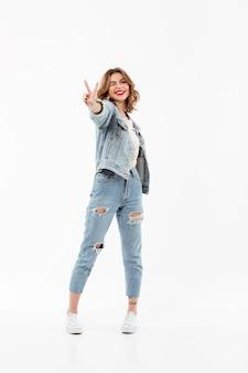 Pleine longueur femme heureuse dans des vêtements en jean clins d'oeil et montrant un geste de paix sur le mur blanc