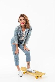 Pleine longueur femme heureuse en vêtements en jean posant avec planche à roulettes sur mur blanc