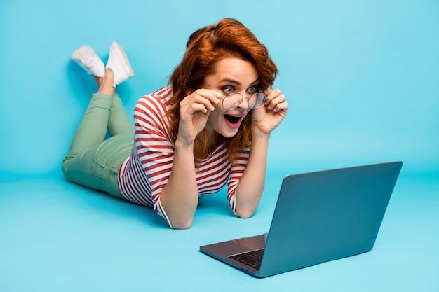 Pleine longueur en gros plan photo impressionné femme folle mensonge plancher utilisation ordinateur lire incroyable blogging notification crier wow omg porter blanc bon look pull isolé couleur bleu