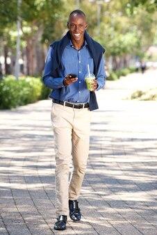 Pleine longueur, homme afro-américain heureux, marche, à, téléphone portable, dehors