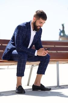 Pleine longueur homme heureux en costume assis sur un banc avec un téléphone mobile