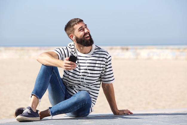Pleine longueur homme heureux dans les écouteurs assis sur la plage avec un téléphone mobile