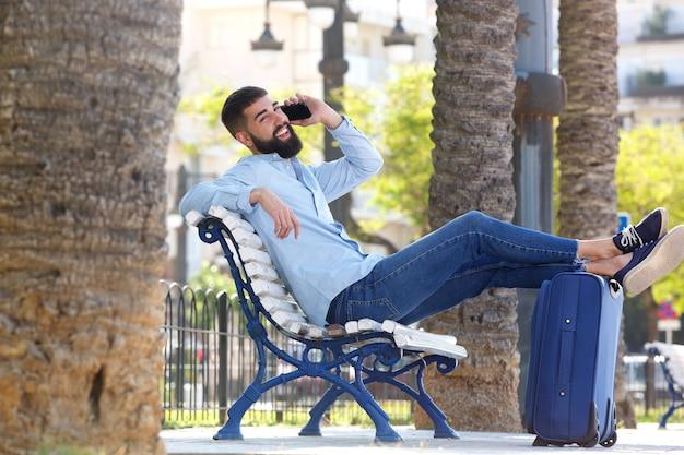 Pleine longueur homme heureux avec valise et téléphone portable à l'extérieur