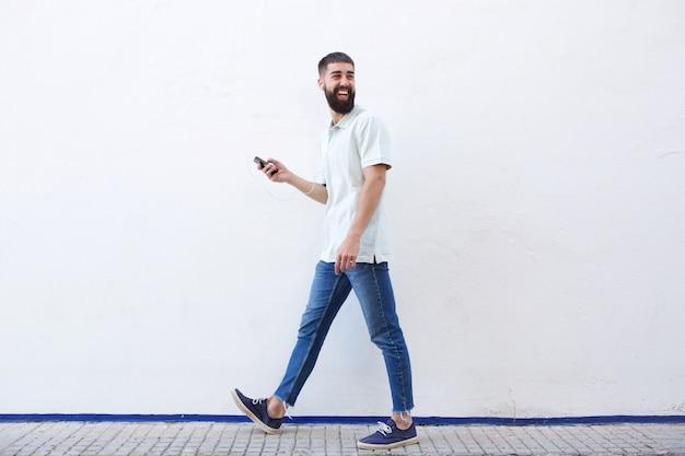 Pleine longueur, homme, marche, tenue, téléphone portable, à, écouteurs