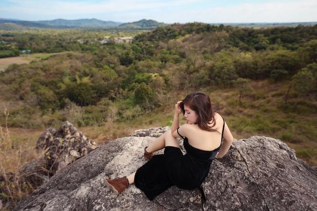 Pleine longueur jeune belle femme asiatique, cheveux longs en robe noire, assis dans la nature en plein air