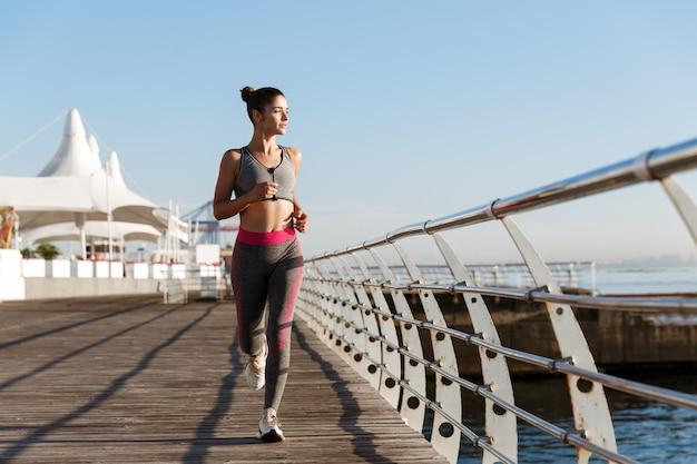 Pleine longueur de jolie femme en forme de jogging le matin, regardant la mer.