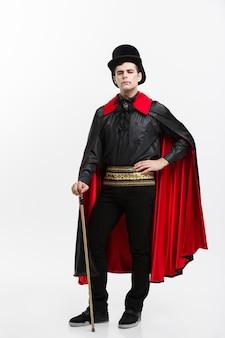Pleine longueur portrait de beau vampire caucasien en costume d'halloween noir et rouge.