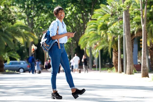 Pleine longueur séduisante jeune femme africaine marche avec sac et téléphone mobile