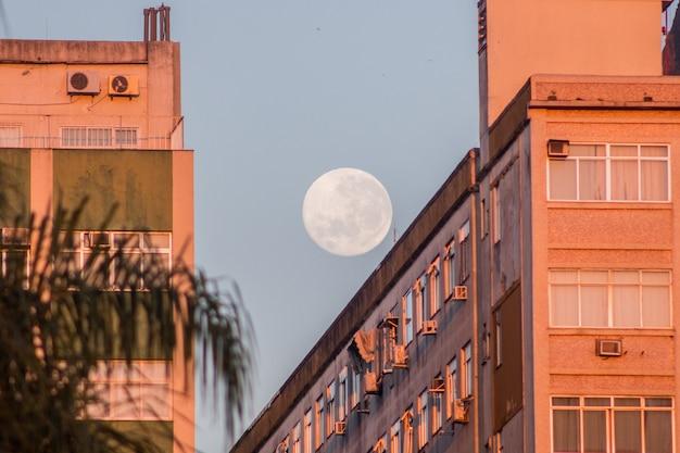 Pleine lune sur un bâtiment sur la plage de botafogo à rio de janeiro, brésil.
