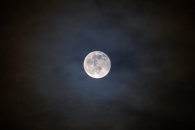 Pleine lune brillante avec des nuages illuminés devant elle.