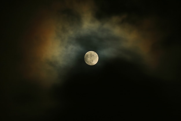Pleine lune sur le ciel sombre avec le clair de lune se reflétant sur les nuages.