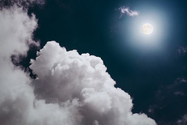Pleine lune avec un gros nuage duveteux dans le ciel nocturne