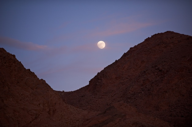 Pleine lune s'élevant sur le désert et les montagnes