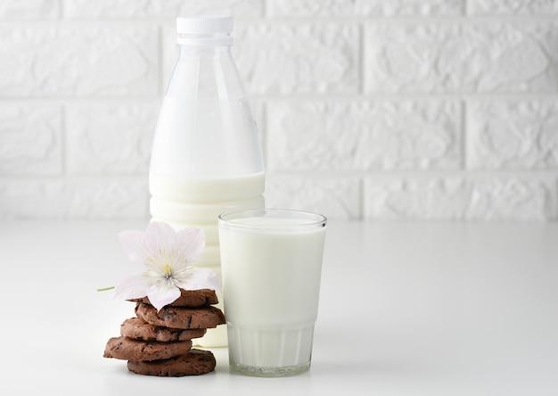 Une pleine tasse de lait en verre et une bouteille en plastique transparent avec du lait, à côté d'une pile de biscuits ronds aux pépites de chocolat sur une table blanche
