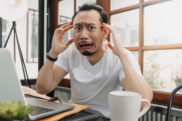 Pleurer et choquer le visage drôle de l'homme décevoir son travail dans son ordinateur portable