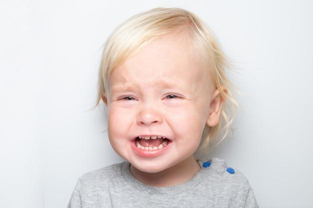 Pleurer un petit garçon caucasien sur blanc