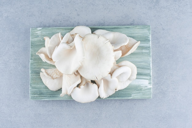 Les pleurotes biologiques frais sur planche de bois.
