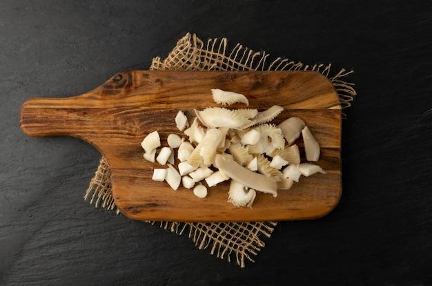Les pleurotes hachés crus sur une planche à découper en bois