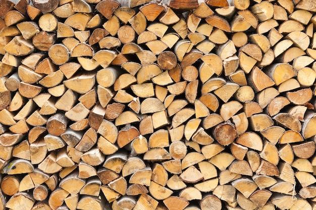 Plié ensemble dans une rangée bûches coupées en morceaux pour brûler au four, gros plan près d'une maison dans le village