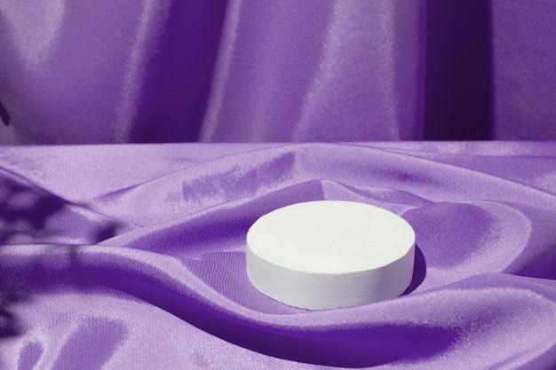 Plis en tissu satiné et podium ou piédestal pour cosmétiques ou parfumerie
