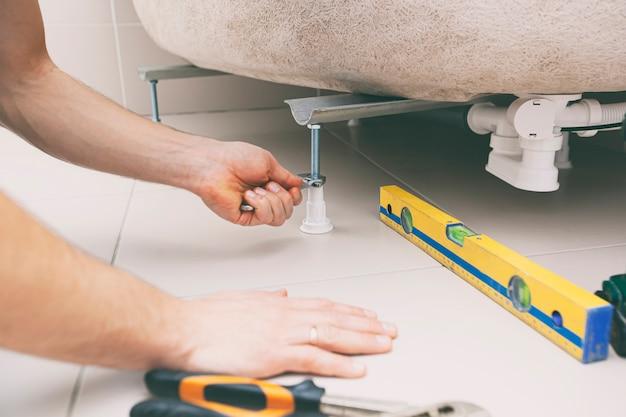 Le plombier ajuste la hauteur de la baignoire