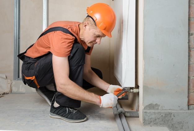Le plombier attachant les tuyaux du système de chauffage au radiateur