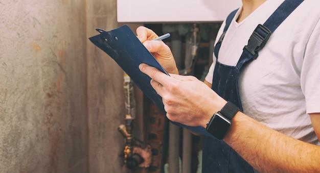 Le plombier calcule le montant des travaux effectués
