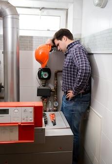 Plombier avec un casque rouge regardant un système de chauffage compliqué