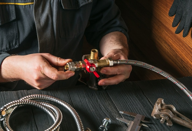 Le plombier connecte les raccords en laiton au robinet de plomberie