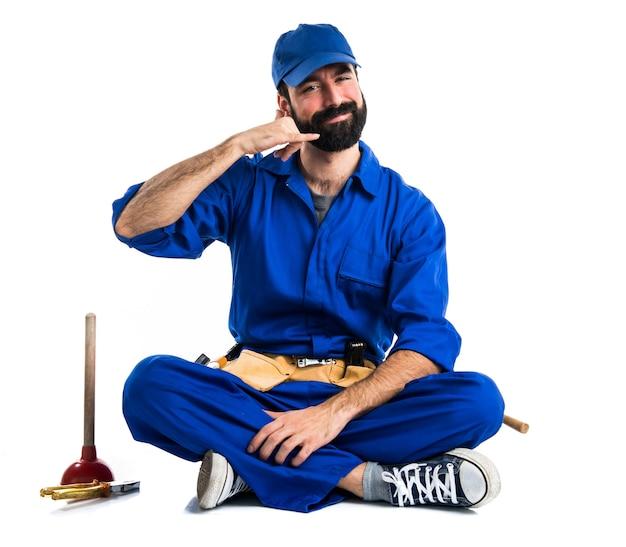 Plombier faisant un geste téléphonique