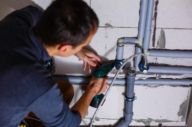 Plombier fait le câblage des tuyaux d'égout