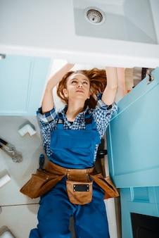 Plombier féminin en uniforme allongé sur le sol dans la cuisine, vue de dessus. bricoleur avec évier de réparation de sac à outils, service d'équipement sanitaire à domicile