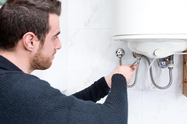 Plombier fixant le chauffe-eau électrique
