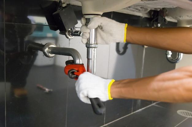 Plombier fixant le tuyau d'évier blanc avec une clé à molette.