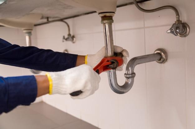 Plombier fixant le tuyau d'évier avec une clé à molette.