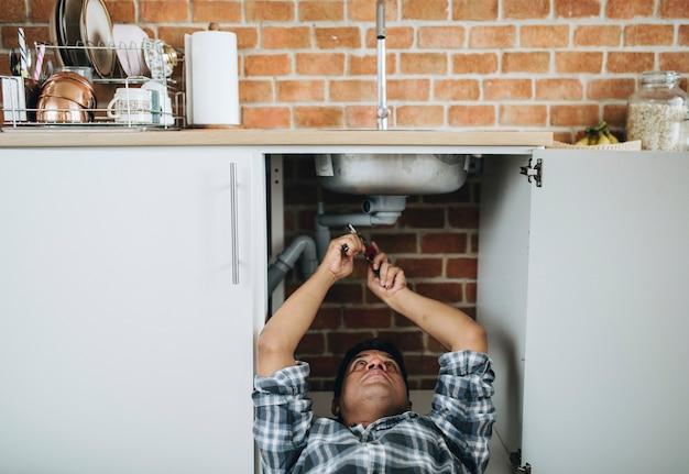 Plombier gisant sur le sol en train de réparer un évier de cuisine