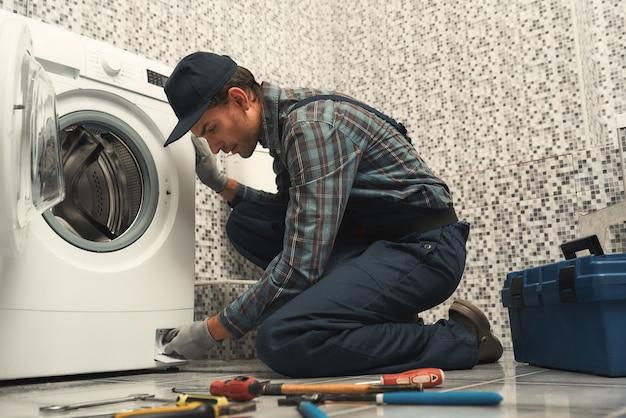 Plombier de haute qualité réparant la machine à laver