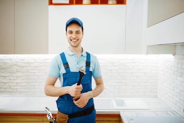 Plombier mâle en robinet de fixation uniforme dans la cuisine. homme à tout faire avec évier de réparation de sac à outils, service d'équipement sanitaire à domicile